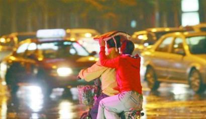 一名坐在车后的女子举起棉垫给骑车男子挡风遮雨 记者 白琳 摄