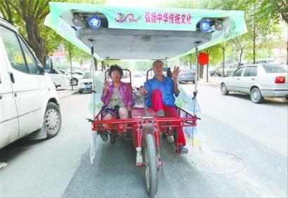 李林祥和他的老伴赵雅范骑着装饰一新的太阳能电动车启程。 记者 查金辉摄
