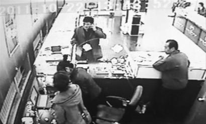 """0月22日,抚顺一家金店被骗子使用39张假币""""买""""走金手镯,金店的监控录像将正在打电话的骗子录下 记者 赵永平 翻拍"""