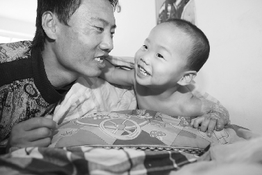 生活艰难,儿子的亲吻就是父亲守护的动力 孙振芳 摄