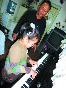 蔡培发正在陪着外孙女练琴 记者 葛洪福 摄