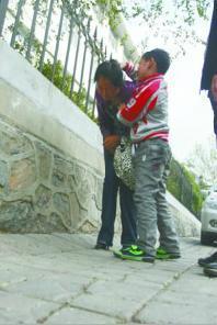 孩子给记者演示妈妈当时被人揪着头发打 记者 张腾飞 摄
