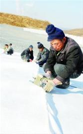 图为工人正在缝合防渗漏的土工布。 本报记者李江摄