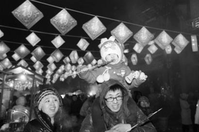 昨晚,在沈阳棋盘山关东影视城内,花灯、冰灯以及各种彩灯吸引了许多游客前来观赏,一个孩子骑在家长的脖子上吃着烤串 记者 白琳 摄