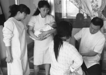 辽宁省专业催乳技术委员会首席催乳师刘相伟(右一)在产妇家进行治疗。 图片由刘相伟 提供