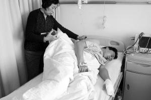 后背受伤的郑先生只能侧躺在病床上,行动很不方便。记者 靳龙 摄
