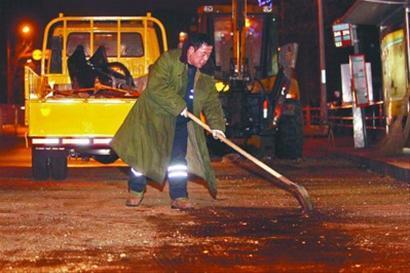 抢修人员正在用细沙覆盖路面的漏油。记者 白琳 摄
