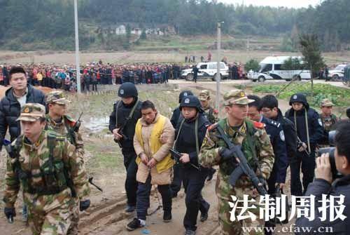 2月9日,犯罪嫌疑人罗汶在民警的押解下前往案发地指认现