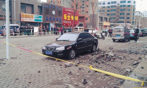 """水泥装饰台""""粉身碎骨"""",被砸到的车很受伤。记者 沈生 摄"""