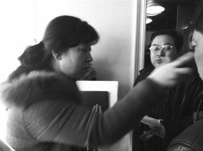 """昨日,""""协商会议""""结束后,家属在电梯口""""堵""""到一位要乘坐电梯离开的沈阳市道口办工作人员(左一),这位工作人员为家属说明协商结果。 记者 李晨溪 摄"""