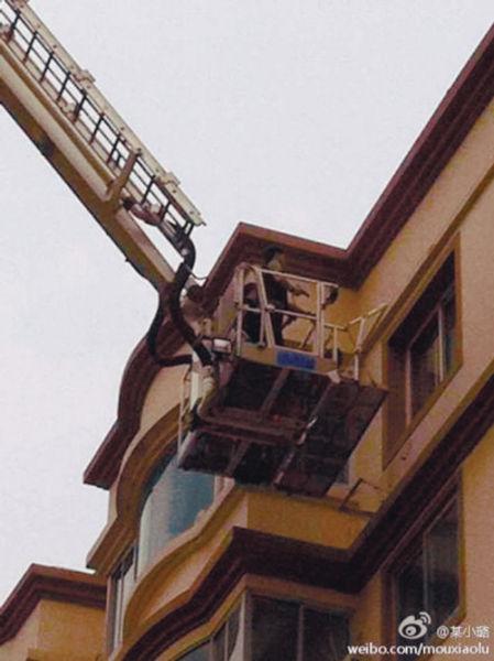 图片显示,两名警察乘坐着消防的云梯进入某一住宅楼的顶楼,然后用枪指向窗口