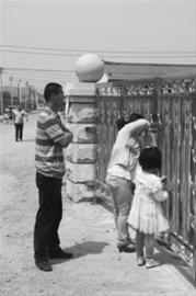 已经命丧车轮下的孩子的父亲庞恒达(左),多次来到幼儿园,要求学校给个说法,但连大门都进不去。 明星记者 栾俊学 摄