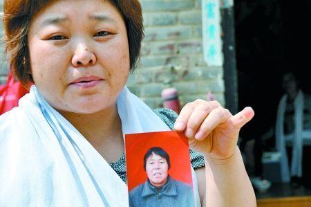 彭秀英的女儿手拿母亲生前的照片。
