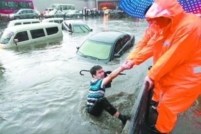 6月2日,在沈阳市和平区与铁西区交界处的南八马路公铁桥下,积水将机动车道吞没,一名被困司机呼喊求救,路边的环卫工人将其拉出水面。 记者 姜旭 摄