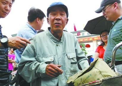 66岁的考生老康一出考场就被家长们围住,老康在说着今年的作文题。