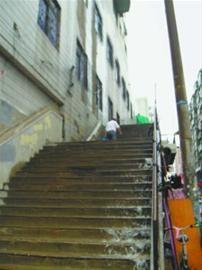 下雨后的100级楼梯面不断有雨水顺梯而下,外出买菜回家的老人艰难地往上爬。 记者 张帆 摄
