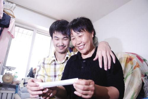 母子俩喜看成绩单。记者 王化威 摄