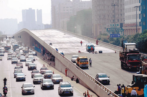 7月2日,工人们正在黄河高架桥上铺设沥青路面。张文魁摄