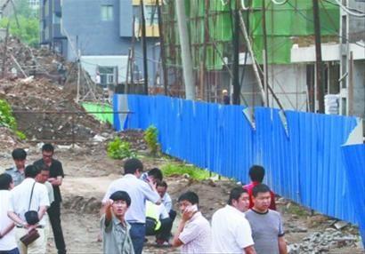 昨日,沈阳市浑南中路一处在建工地旁,一名男子被高空坠物砸死。警察正在勘察现场,工地保安示意记者禁止拍照。 记者 于岛 摄