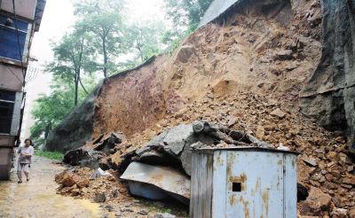坍塌的护坡墙离居民楼很近,掩埋住了墙下的一座简易棚和几辆摩托车。