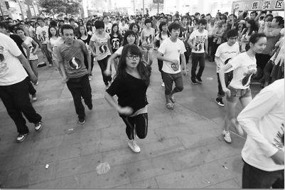 7月15日晚7时30分,中街步行街上,随着召集方音乐准时响起,百名青年立即自动组成队形,随着《billie jean》的音乐节拍扭动起身体。舞者中几乎都是年轻人,其中有男有女,舞步娴熟,引来很多路人围观。 吴怀宇 摄