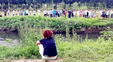 昨日,落水环卫工人的儿媳蹲在老人落水的岸边,望着湍急的河水流眼泪。 记者 刘晓 摄