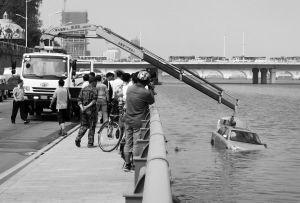 用吊车打捞掉进浑河里的轿车。