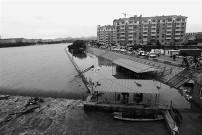 昨晚7时许,在大凌河建昌县水上公园河段,一些冲下的垃圾堆积在滚水坝处,一旁临水的人行道积水还未退去。 本版图片由记者 白琳 摄