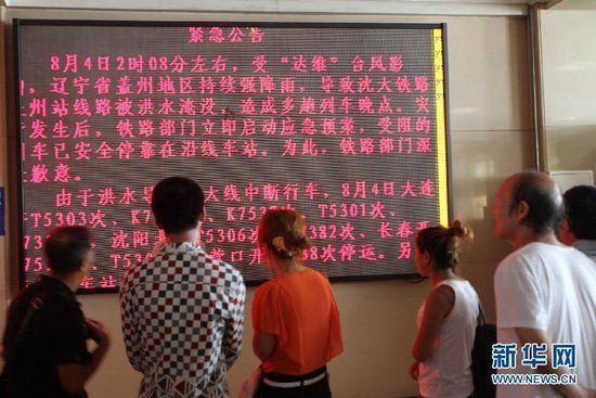 8月4日,乘客在大连火车站阅读关于列车停发的公告。