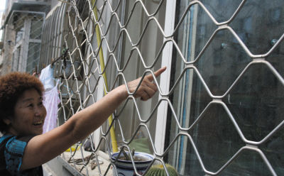 居民指着自家窗户遭袭留有的明显弹痕(画圈处)。