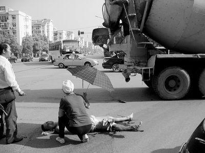 """图为过路女子为伤者撑伞遮阳。网友""""武汉欢迎你"""" 摄"""