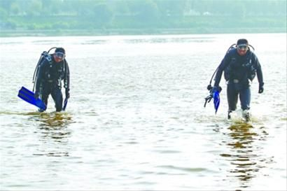 """昨日下午4时22分,在沈阳浑河,""""蛙人""""没有搜寻到失踪的小伙孟凡星,两人低着头回到岸边。 记者 查金辉 摄"""