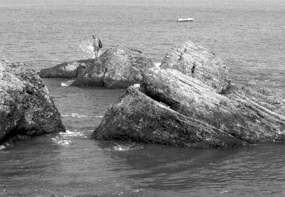 穿着游泳短裤的张大叔站在距离海岸不到100米远的一片礁石上。