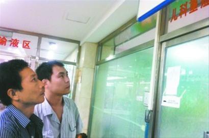 昨日中午,盛京医院重症监护室外,孩子的父亲和好心司机(右)一起焦急地等待着误服药物孩子的情况。 记者 王迪 摄
