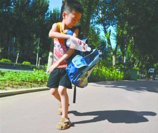 虽然已经是暑假了,但9岁的王昊天每天都背着大书包在街上捡着饮料瓶。 张立军 摄