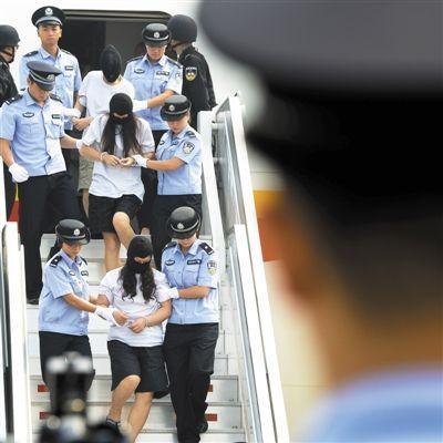 昨日,在北京首都国际机场,涉案犯罪嫌疑人被押解下飞机。新华社记者 戚恒 摄
