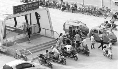 9月2日下午3时50分许,在沈阳地铁一号线黎明广场站,D出入口门前聚集着许多拉脚等活的司机。 记者 查金辉 摄