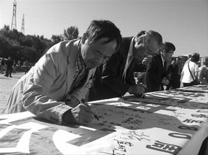 昨日抚顺纪念平顶山惨案80周年,日本友人、中国人战争被害赔偿请求事件律师团成员小野寺利孝(中间的老人)在纪念条幅上签字。 首席记者赵永平摄