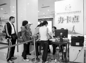 市民排队办公共自行车借车卡■本报记者 杨大海 摄