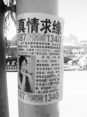 """电线杆上的""""富婆求子""""广告中不仅有公证号还盖着公章 ■本报记者 张毅 摄"""