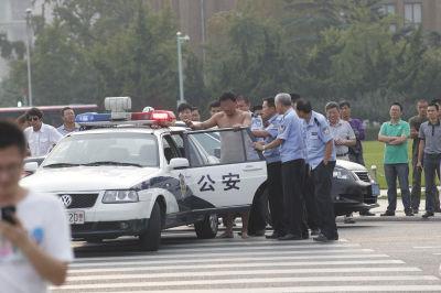 民警最终将该男子带上警车离开。