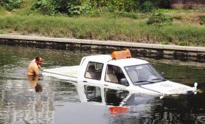 驾校的工作人员检查掉入水中的教练车
