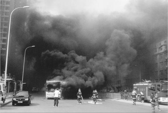公交车行驶途中起火,消防员正在扑救。