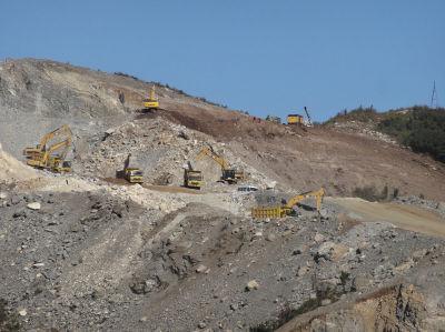 """遗址被大量挖掘机""""蚕食""""掉半个山坡。"""