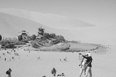10月4日,游人在敦煌鸣沙山月牙泉景区游览。新华社发