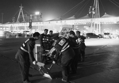 """昨晚11时许,在沈丹高速沈阳站收费口,工作人员将""""7座及以下小型客车通道""""的提示牌移走。 主任记者 吴章杰 摄"""