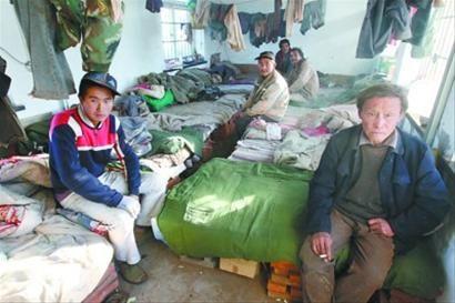 """几名工人坐在用红砖搭起的""""床""""上,他们每天要工作接近十二个小时。 本版图片由记者 吴怀宇 摄"""
