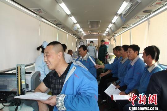 图为郭明义爱心团队队员代表,穿着整齐的工作服,排队走上无偿献血车,将鲜红的爱心献给需要帮助的人。 记者 秦逸 摄