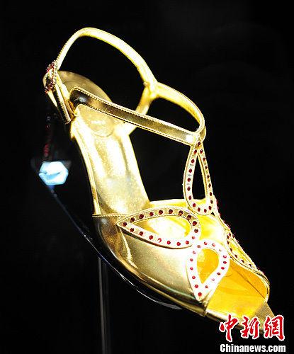 """10月26日,在辽宁省沈阳市市府恒隆广场展出一款名为""""加冕鞋"""",这双鞋是复制了1953年为伊丽莎白二世女王陛下登基特别设计的加冕鞋,并装饰以红宝石色的华美水钻。中新社发 于海洋 摄"""