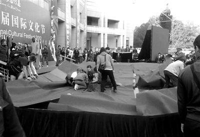 """舞台坍塌现场。昨日,在北大国际文化节开幕结束后,几名学生在跳《江南style》的""""马步舞""""时,舞台坍塌。 网友供图"""